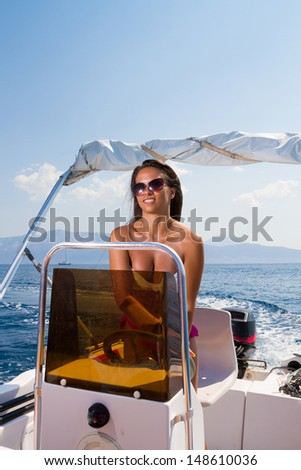 A stunningly beautiful young woman driving a speedboat and having fun.