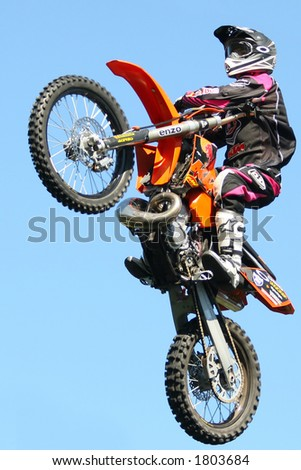 A stunt rider doing tricks on his dirt bike - stock photo