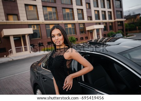 A stylish business lady is standing next to a car in black. Fashion. Auto.
