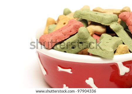 A stylish dog bowl filled with the mans best friends treat. - stock photo