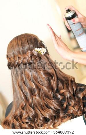 A stylist and a makeup artist is using hairspray on beautiful long blonde hair of a young woman during the preparation. Selective focus - stock photo