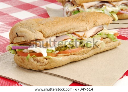 A sub sandwich with ham, beef, turkey and cheese - stock photo