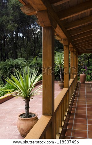 A sub tropical wooden patio near bush and grass. - stock photo
