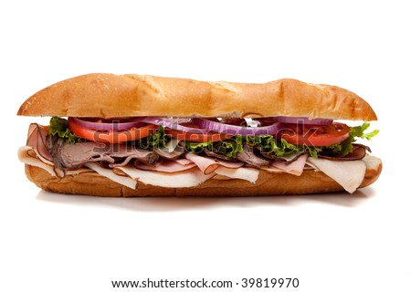 A submarine sandwich including ham, turkey, roast beef, tomato, lettuce, onion and cheese on a french bun on a white background