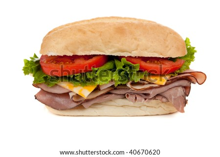A submarine sandwich with ham, turkey, roast beef,  lettuce, tomato and swiss cheese on a white background - stock photo