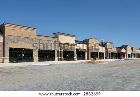 A suburban shopping center under construction.  A row of storefronts. - stock photo