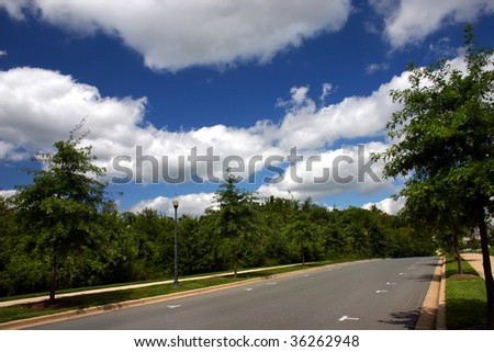 a suburban street with beautiful clouds in the sky - stock photo