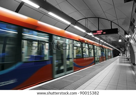 A subway train in motion arriving at a London underground train station. - stock photo