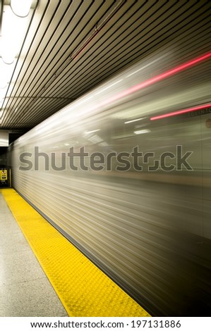 A subway train speeding past the yellow floor.