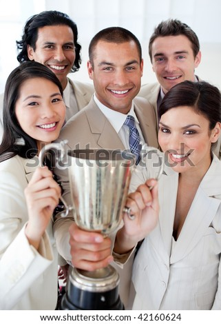 A successful business team holding a trophy. Concept of success. - stock photo