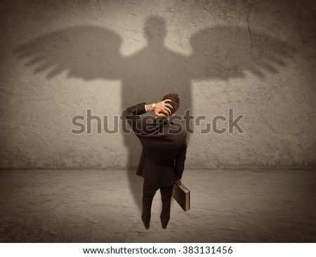 A successful businessman holding a briefcase is giving thumbs up for his angel shadow in front of a wall concept - stock photo