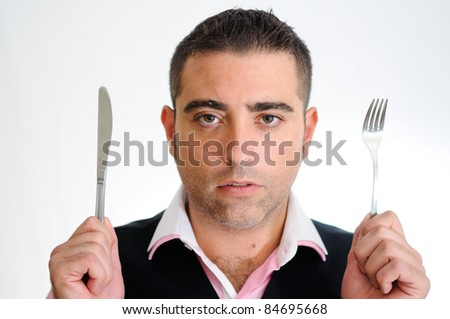 A successful businessman wearing vest and pink shirt looking with a knife and a fork. - stock photo