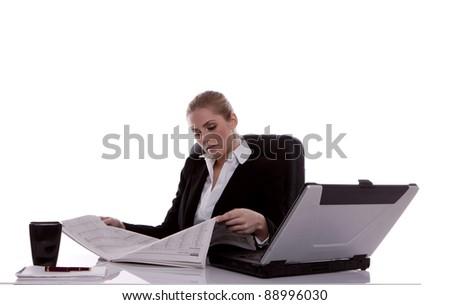 A successful businesswoman sitting at her desk reading a financial newspaper. Businesswoman.
