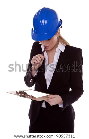 A successful businesswoman standing and wearing a blue safety hardhat. Businesswoman