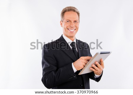 A successful mature manager with ebook in his hands