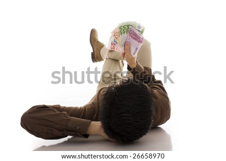 A sucessful business man lying on the floor looking to euros banknotes