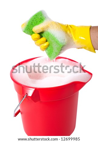 A sudsy bucket or pale of soap with a hand holding a sponge. cleaning concept or chores