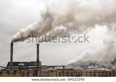 a sugar mill polluting the atmosphere with smoke and smog - stock photo