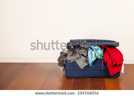 A suitcase overflowing with clothes - stock photo