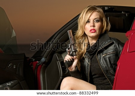 A sultry, blond woman, dressed in black, is getting out of a red sports car holding a revolver. - stock photo