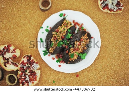 A summer appetizer of baked eggplant stuffed with nuts, decorated with pomegranate seeds, parsley and cilantro on a white plate on a cork table, top view. - stock photo