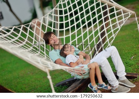 a summer day on the nature of the father and son rest in the big white hammock - stock photo