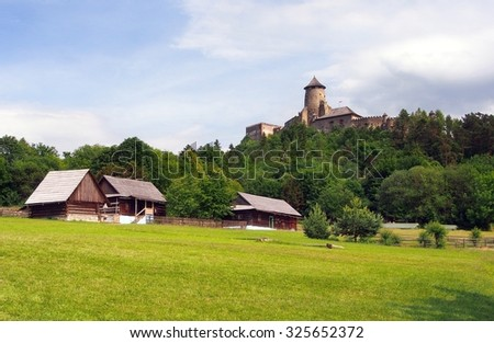 A summertime view of authentic, centuries old folk houses located in the open-air museum of Stara Lubovna, Spis region, eastern Slovakia. The famous castle of Lubovna can be seen in the background.