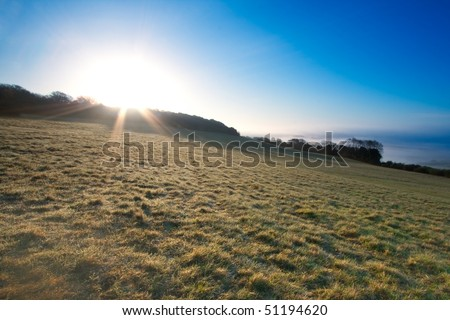 A sunburst over a field.  Taken just after dawn at Newlands Corner near Guildford in Surrey, UK. - stock photo