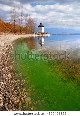 A sunny autumn day view portraying shore of the Liptovska Mara lake, with green algae in the water. The hills of Western Tatras, Rohace mountains, can be seen in the distance.