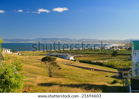 A sunny holiday resort area in northern New Zealand, with coast line and local orchard.