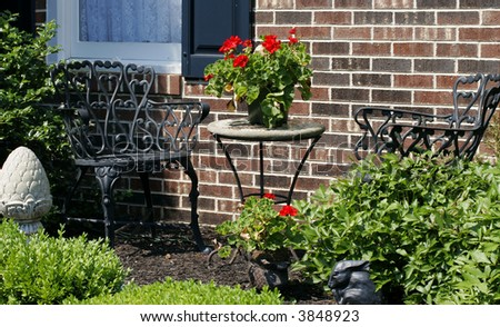 a sunny patio with an iron dining table and chairs - stock photo
