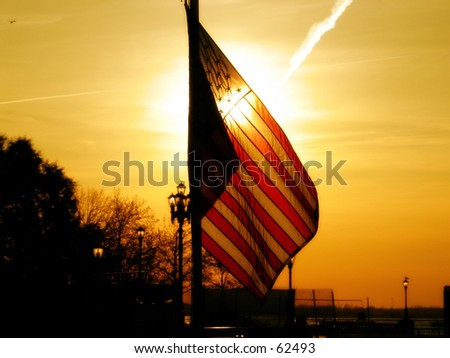 a sunset background in ny with the american flag - stock photo