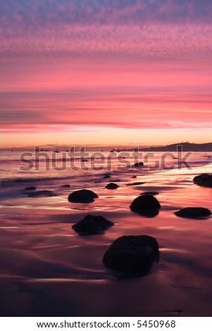 A sunset during low tide along Butterfly Beach in Santa Barbara, CA. - stock photo