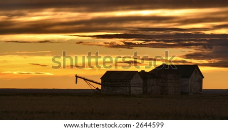 A sunset in a field with some barn farmyard buildings - stock photo