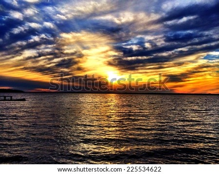 A sunset in a partly cloudy sky over rippling water. - stock photo