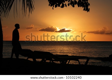 a sunset in Barbados with the silhouette of a man and two sunbeds, focussed on the man with slightly de-focused clouds - stock photo