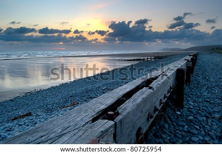 a sunset over the sea and the pebble beach in Borth, Wales UK