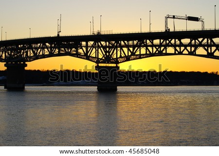 A sunset silhouetted bridge and river bank at sunset.
