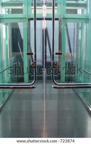 A super slick chrome and glass doorway leads to the mega tech elevator of the future.  Or you could just say - A doorway leading to an elevator... - stock photo