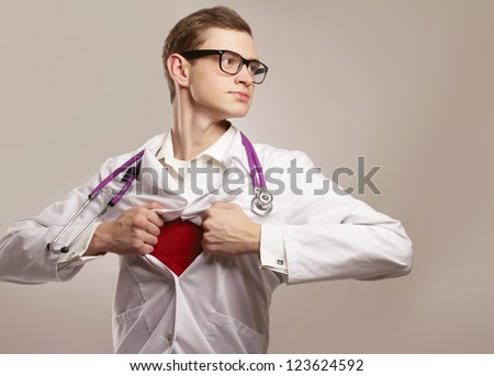 A superhero doctor is looking forward on grey background