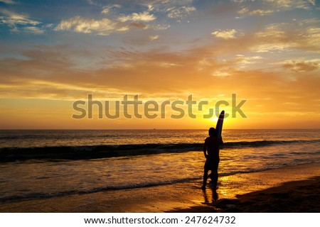 A surfer admires the last waves of the day at sunset. - stock photo