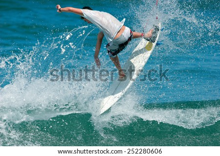 A surfer executes a radical backhand aerial move on an ocean wave. - stock photo