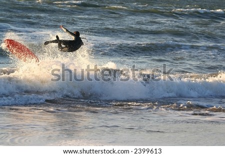 A surfer falling off his board. - stock photo