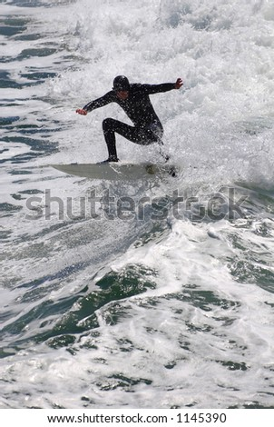 A surfer gets air off a beautiful wave on the coast of California. - stock photo