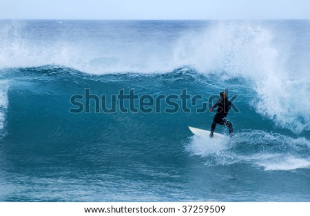 A surfer in a black wetsuit rides a wave