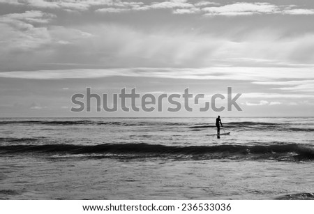 A surfer in Malibu heading out into the Pacific. - stock photo