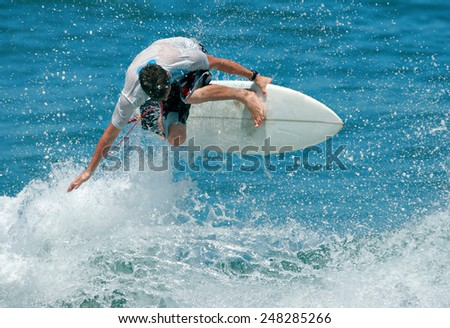 A surfer launches a radical backhand aerial on a wave. - stock photo