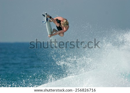 A surfer launches into the air above a beautiful blue wave, executing a radical aerial maneuver. - stock photo