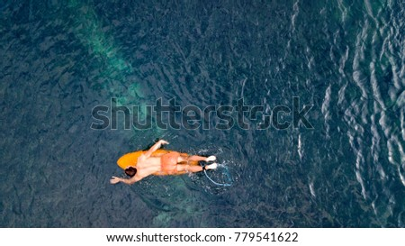 A surfer paddling through the clear tropical waters over the reef at Serangan Island, in Bali, Indonesia.