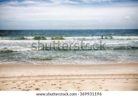 A surfer rides in a wave at Kure Beach, North Carolina. - stock photo